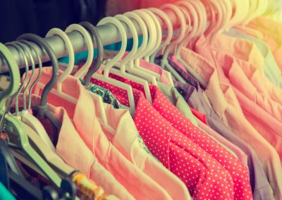 Clothes hang on a shelf in a designer clothes store in retro col